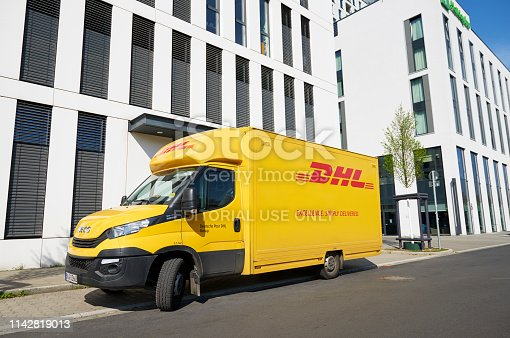 Duesseldorf, Germany- April 10, 2019: A DHL delivery truck (Iveco) in front of white office buildings at the Duesseldorf quarter