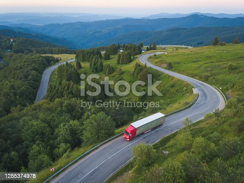 Big truck of delivery company with cargo is driving on forest road in the mountains at sunset.