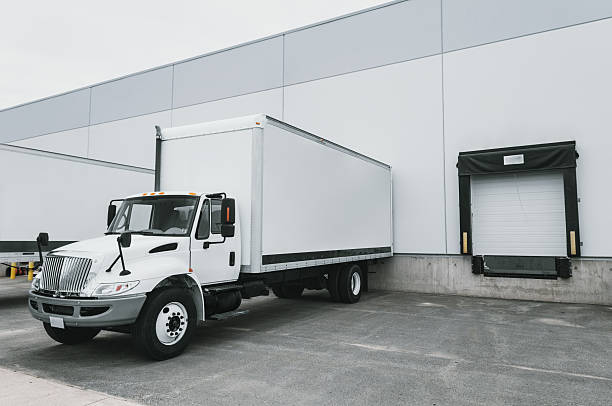 delivery trucks at warehouse - lorries unloading stock photos and pictures