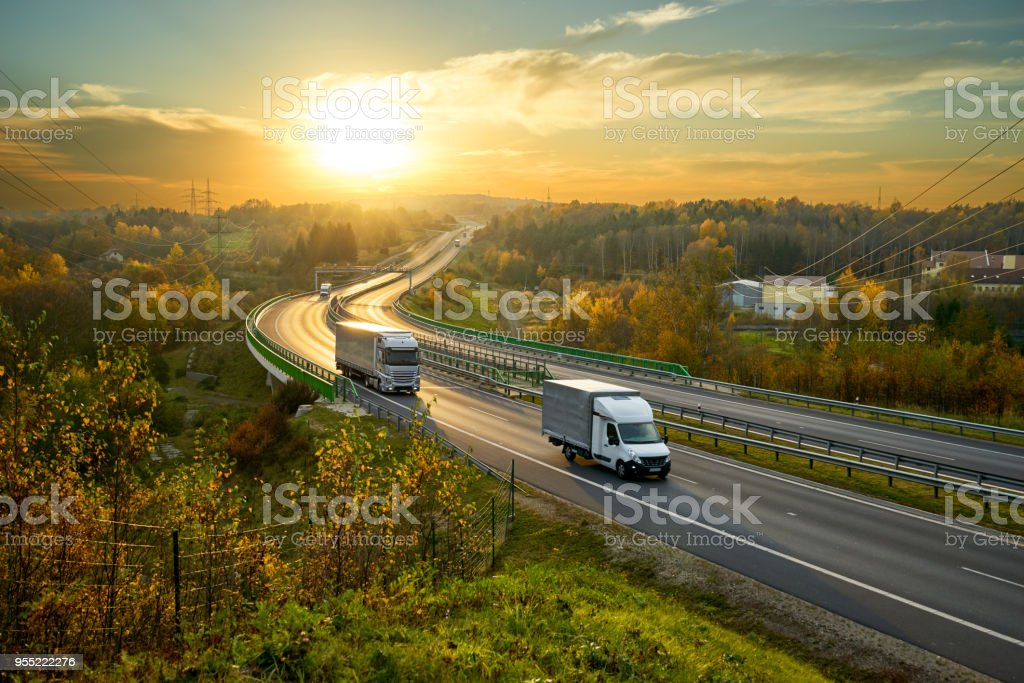 Delivery van and truck driving on the highway winding through forested landscape in autumn colors at sunset - Royalty-free Autumn Stock Photo
