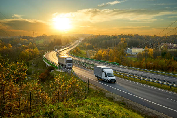 lieferwagen und lkw-fahren auf der autobahn schlängelt sich durch bewaldete landschaft in herbstlichen farben bei sonnenuntergang - pickup trucks stock-fotos und bilder