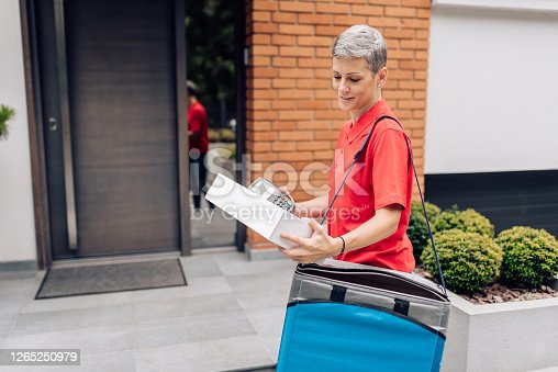 Delivery woman bringing the order to the customer's door.