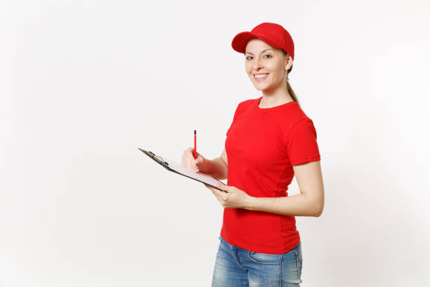 Delivery woman in red uniform isolated on white background. Female in cap, t-shirt, jeans working as courier or dealer, holding pen, clipboard with papers document, with blank empty sheet. Copy space. stock photo