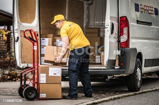 Delivery woman stacking packages from van on cart.