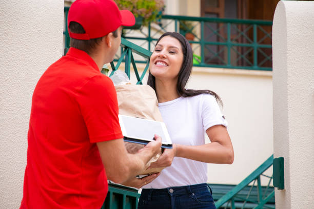 Deliveryman delivering food to happy female customer stock photo