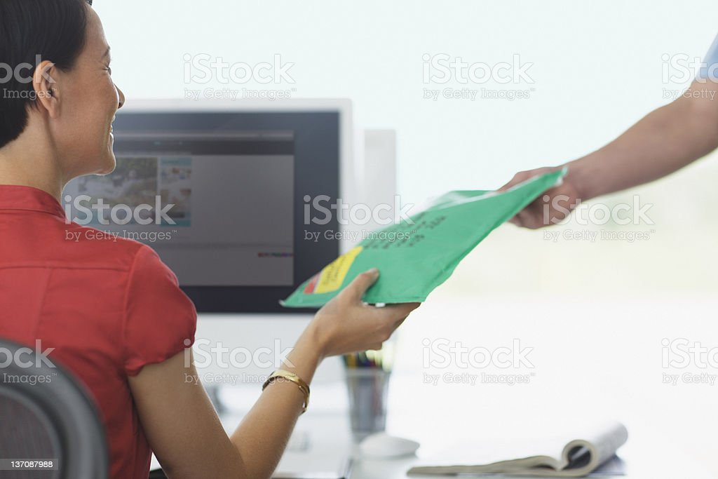 Deliveryman handing package to businesswoman royalty-free stock photo