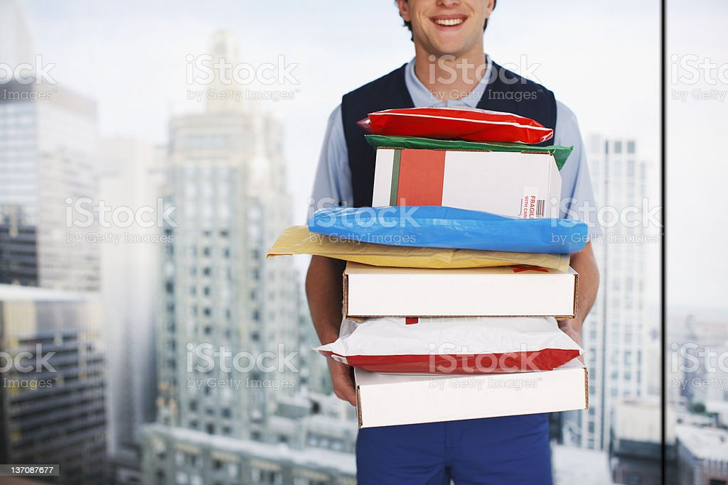 Deliveryman holding stack of packages stock photo