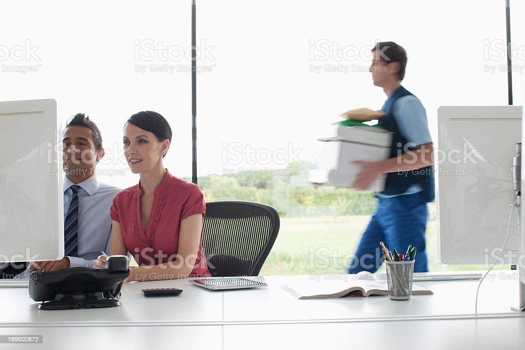 Deliveryman walking past business people working in office royalty-free stock photo
