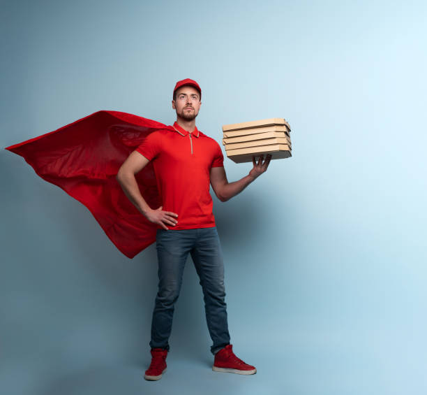 Deliveryman with pizzas acts like a powerful superhero. Concept of success and guarantee on shipment. Studio cyan background - foto stock