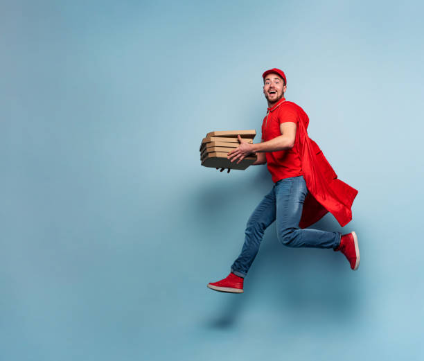 Deliveryman with pizzas acts like a powerful superhero. Concept of success and guarantee on shipment. Studio cyan background stock photo