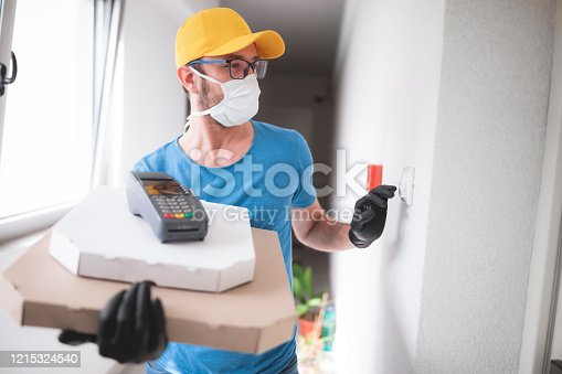 Deliveryman with protective medical mask holding pizza box and POS wireless terminal for card paying, ringing at the doorbell - days of viruses and pandemic, food delivery to your home and safety hygiene measures.