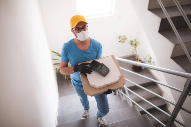 Zusteller mit schutzmedizinischer Maske hält Pizza-Box und POS Wireless-Terminal für Kartenzahlung - Tage der Viren und Pandemie, Lebensmittellieferung zu Ihrem Haus und Sicherheitshygienemaßnahmen. – Foto
