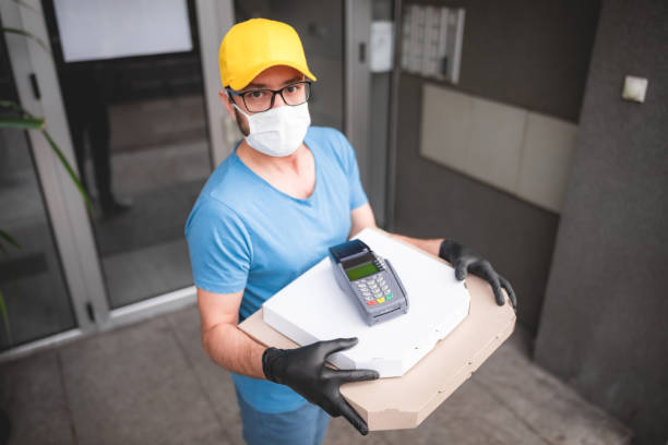 deliveryman with protective medical mask holding pizza box and pos wireless terminal for card paying - days of viruses and pandemic, food delivery to your home and safety hygiene measures. - essential workers stock pictures, royalty-free photos & images