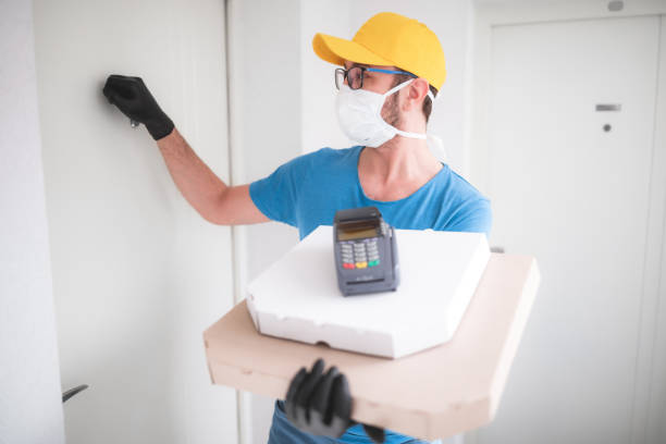 Deliveryman with protective medical mask holding pizza box and POS wireless terminal for card paying, knocking at the door - days of viruses and pandemic, food delivery to your home and safety hygiene measures. stock photo