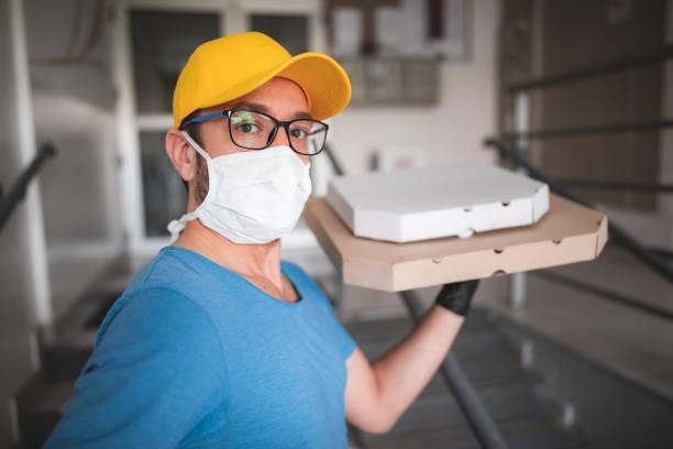 Zusteller mit schützender medizinischer Maske hält Pizza-Box - Tage der Viren und Pandemie, Lebensmittellieferung zu Ihnen nach Hause. – Foto