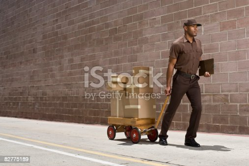 istock delivery-person carrying boxes on toy wagon 82775189