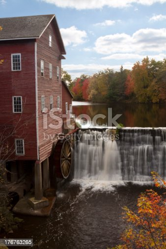 An old mill next to a dam in autumn.