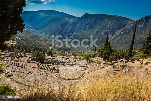 Delphi, Greece - July 1, 2018: Ancient Historical ruins with the Delphi Theater and Apollo's temple with Phocis valley in background and the Mount Parnassus, Greece. You can see tourists on a site.