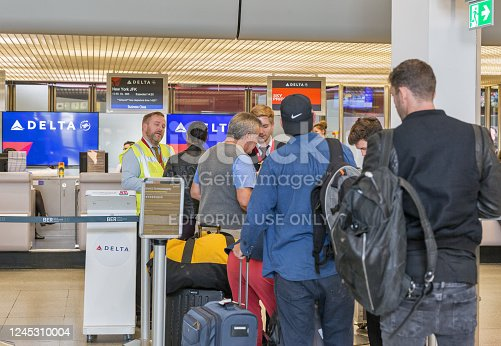 BERLIN, GERMANY - OCTOBER 18, 2019: Passengers check in with luggage for flight to New York JFK at the Delta Air Lines desk in Tegel Airport, the main international airport of the capital of Germany.