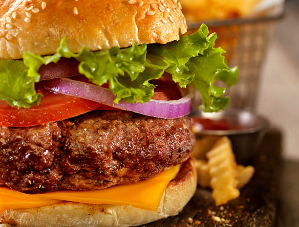deluxe cheeseburger with a basket of fries - kräuterfaltenbrot stock-fotos und bilder