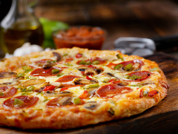 Deluxe Pizza with Pepperoni, Sausage, Mushrooms and Peppers stock photo