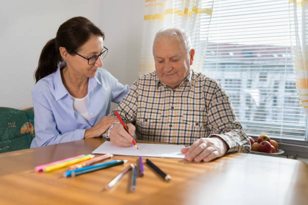 Dementia and Occupational Therapy - Home caregiver and senior adult man stock photo