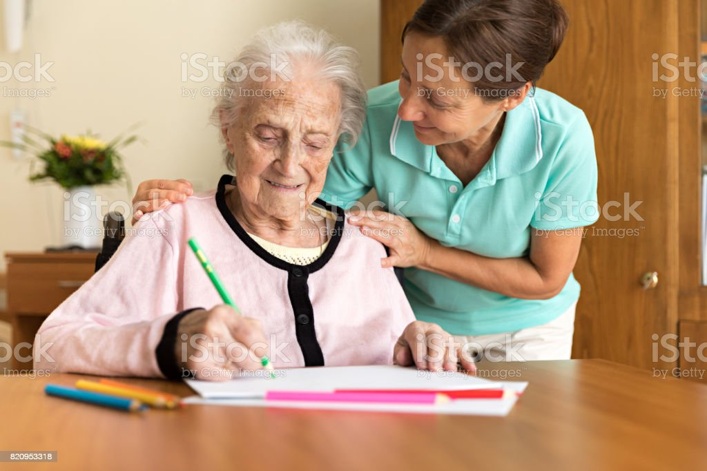 Dementia and Occupational Therapy - Home caregiver and senior adult woman stock photo