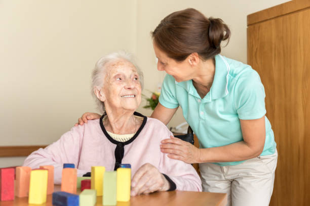 Dementia – Home Caregiver and Senior Adult Woman stock photo