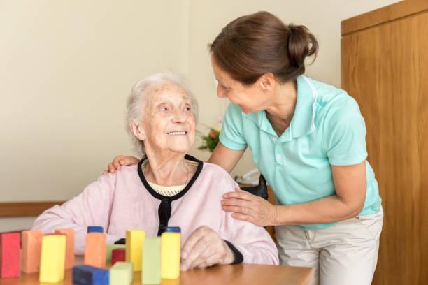 Demenz – Heimpflegerin und ältere Erwachsene – Foto