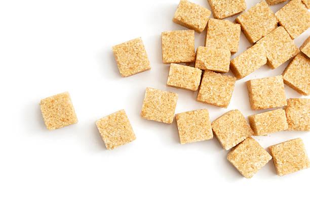 demerra sugar lumps verstreut - würfelzucker stock-fotos und bilder