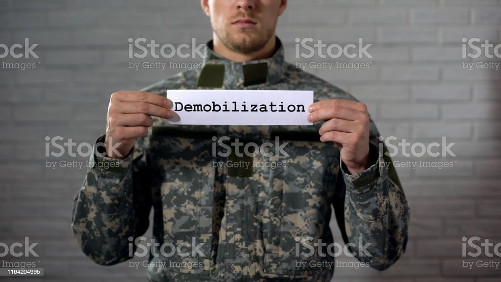 Demobilization word written on sign in hands of male soldier, end of...