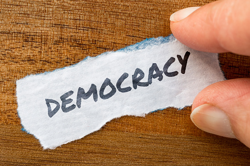 istock Democracy concept and theme written on old paper on a grunge background 896288144