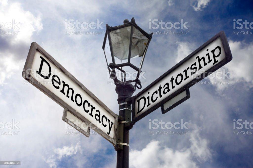 Democracy Vs. Dictatorship Street sign illustrating the concept of Democracy versus Dictatorship. Authority Stock Photo