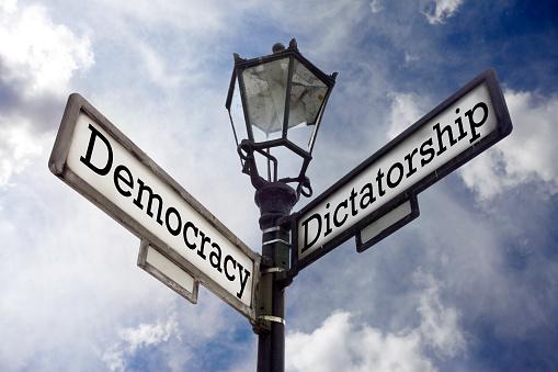 Street sign illustrating the concept of Democracy versus Dictatorship.