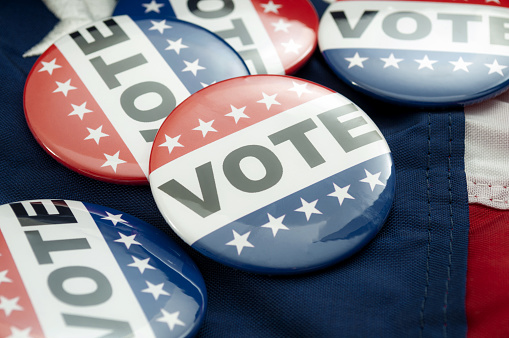 istock Democrat vs republican poll, democratic decision and primary voting conceptual idea with Vote election campaign button badges and the united states of american flag 1183053829