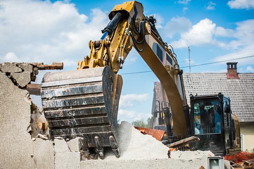 Mechanical digger demolishing building.
