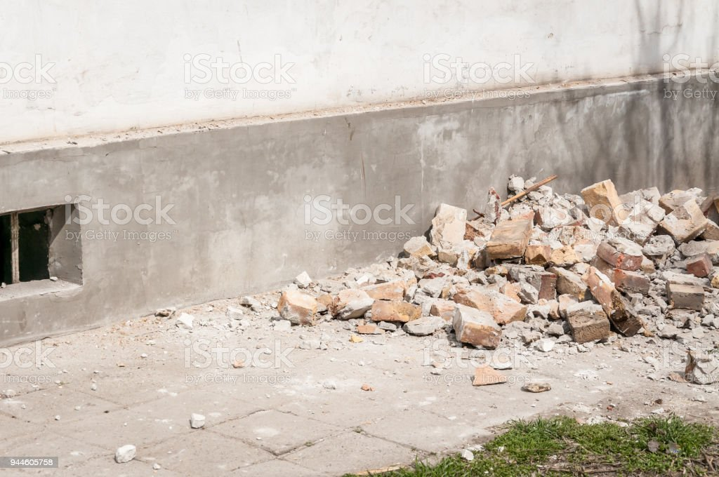 Demolition and destruction site bricks remains of building material on the ground by the house foundation base stock photo