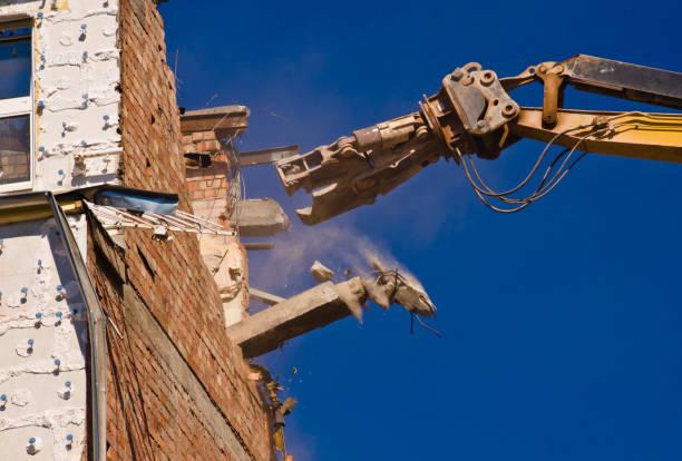 une démolition d'un bâtiment avec une grue avec un fond bleu de ciel - imploser photos et images de collection