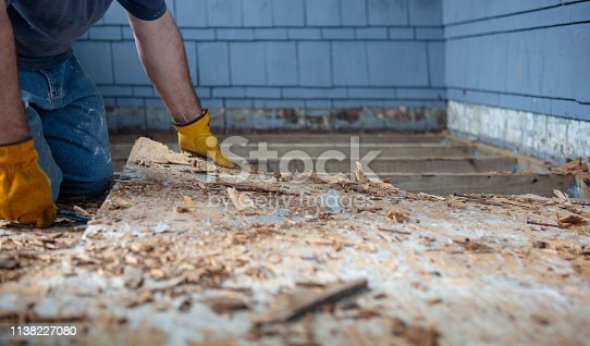 Workman using crowbar to pry up rotten wooden deck or porch