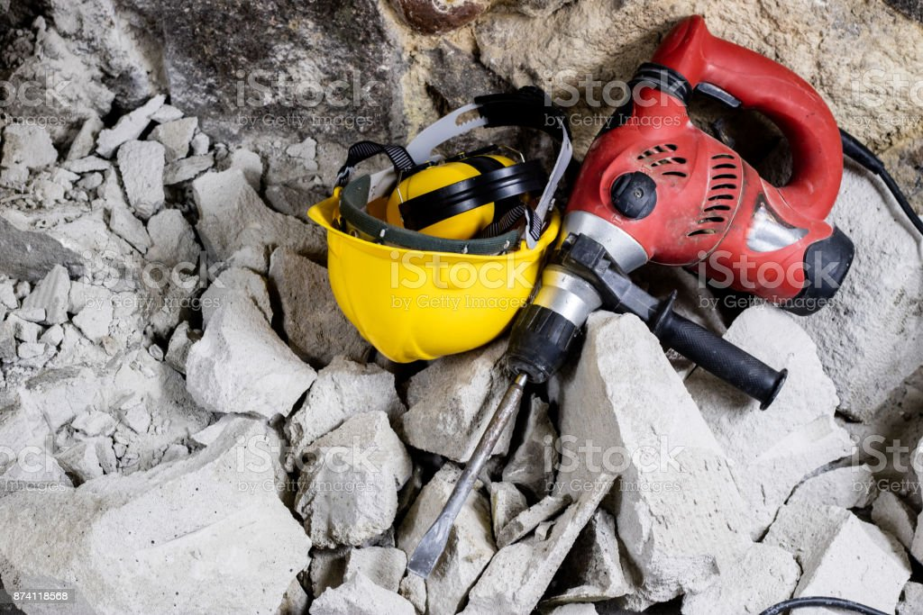 Demolition of walls. Electric hammer helmet and hearing protection lying on the rubble. Old brick and remodeled building wall. Grunt on the background of the old wall. stock photo