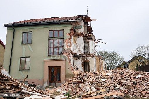 Half a house. Demolition / tear down a house made of bricks. A big pile of bricks and scrap.
