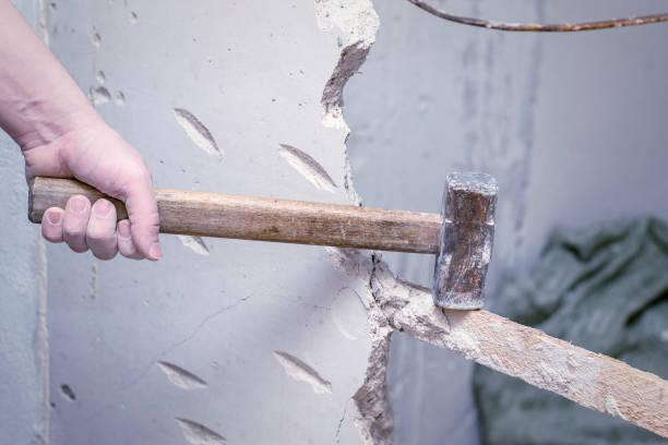 demolition work and rearrangement. worker with sledgehammer destroying wall stock photo