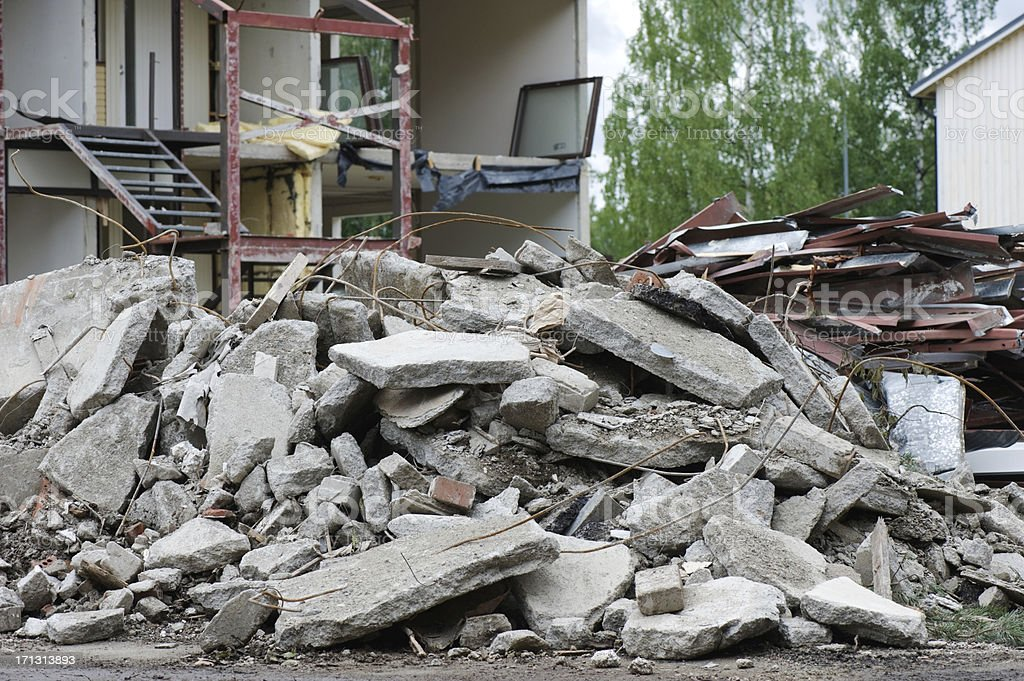 Demolition work Pile of concrete in front of partially demolished house. Focus on foreground. Accidents and Disasters Stock Photo