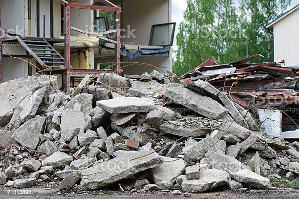 Pile of concrete in front of partially demolished house. Focus on foreground.