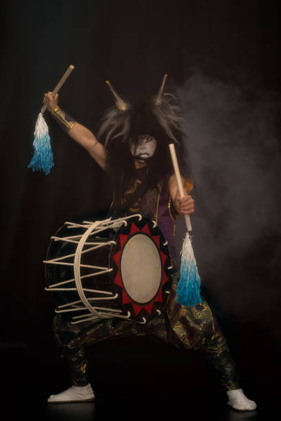 demon from japanese mythology. full lenght portrait of an artist drummer taiko in a wig with horns and make-up drum on stage against a dark background. - theatre full of people stage foto e immagini stock