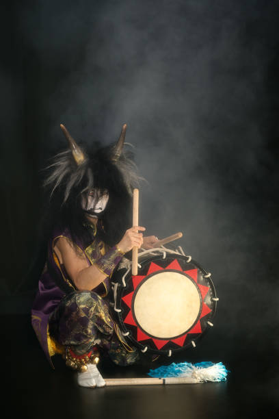demon from japanese mythology. full lenght portrait of an artist drummer taiko in a wig with horns and make-up sits on stage against a dark background. - theatre full of people stage foto e immagini stock