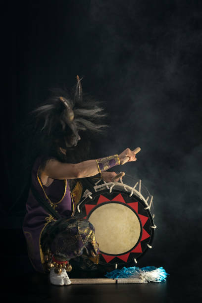 demon from japanese mythology. full lenght portrait of an artist drummer taiko in a wig with horns and make-up sits on stage and shakes head against a dark background. - theatre full of people stage foto e immagini stock