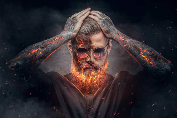 Demonic male with burning beard and arms. stock photo