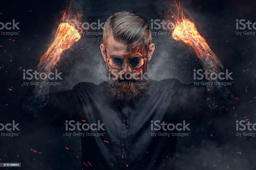 Demonic man with burning arms. stock photo