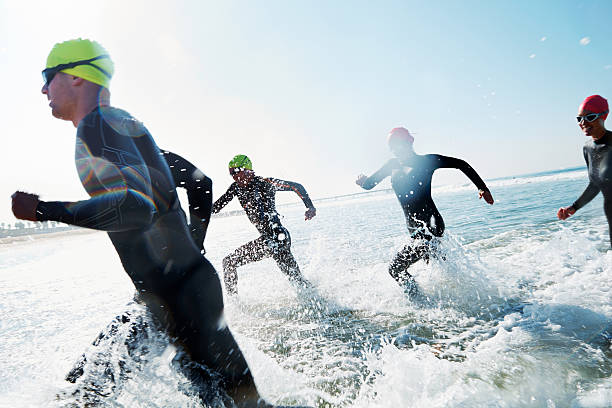 Demonstrating endurance A group of athletes competing in a triathlon wetsuit stock pictures, royalty-free photos & images